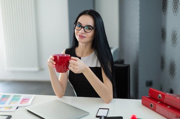 Una giovane e graziosa donna d'affari in abito nero e occhiali si siede al tavolo e tiene in mano una tazza rossa