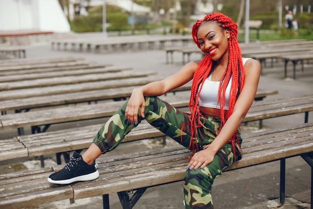 Una giovane ed elegante ragazza dalla pelle scura con il rosso teme seduto nel parco estivo