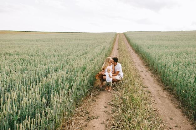 Una giovane famiglia si diverte con il loro piccolo bambino sul campo