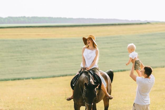 Una giovane famiglia si diverte sul campo. genitori e bambino con un cavallo