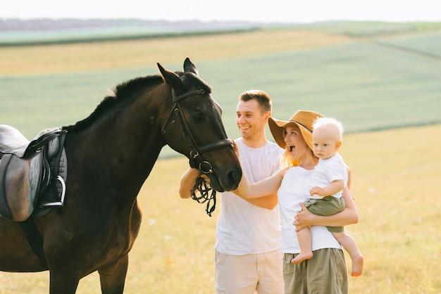Una giovane famiglia si diverte sul campo. genitori e figlio con un cavallo