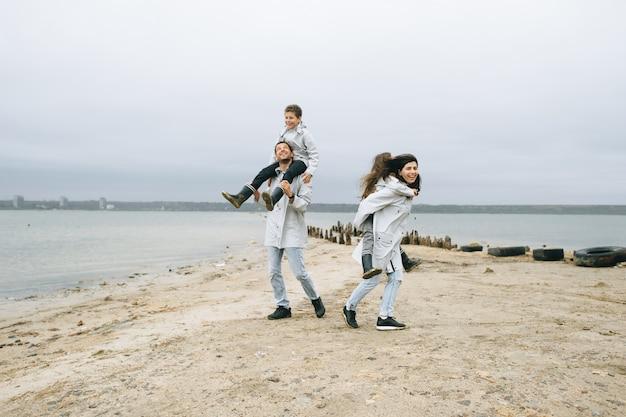 Una giovane famiglia si diverte vicino al mare su uno sfondo di barca