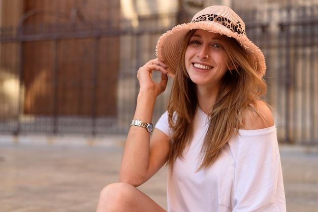 Una giovane femmina attraente con un top bianco carino e jeans seduti sulle scale e godersi il bel tempo