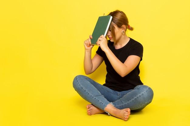 Una giovane femmina di vista frontale che si siede in camicia nera e blue jeans che tengono il quaderno verde su colore giallo