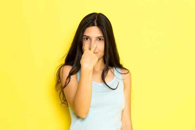 Una giovane femmina di vista frontale in camicia blu che posa che indica nei suoi occhi sullo sfondo giallo ragazza posa modello bellezza giovane