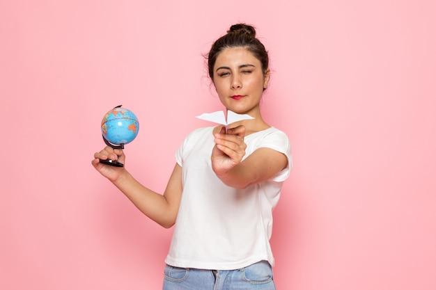 Una giovane femmina di vista frontale in maglietta bianca e blue jeans che tengono aereo di carta e piccolo globo