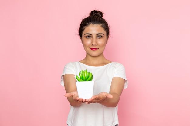Una giovane femmina di vista frontale in maglietta bianca e blue jeans che tengono poca pianta