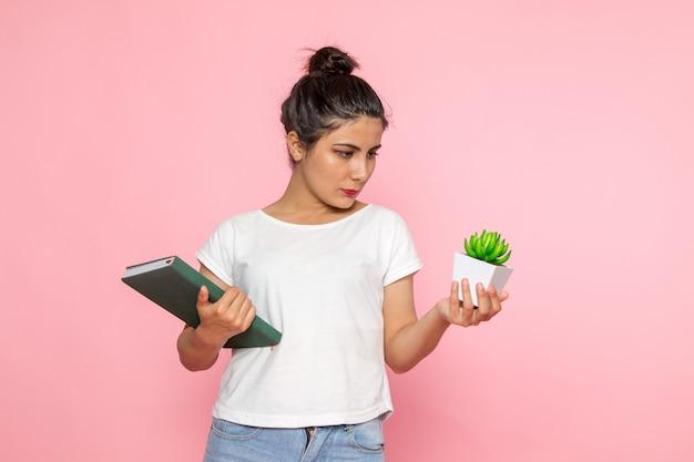 Una giovane femmina di vista frontale in maglietta bianca e blue jeans che tengono quaderno e pianta