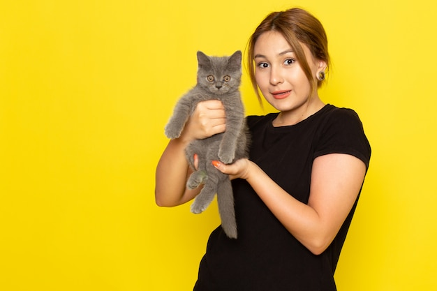 Una giovane femmina di vista frontale in vestito nero che tiene piccolo gattino sveglio su colore giallo