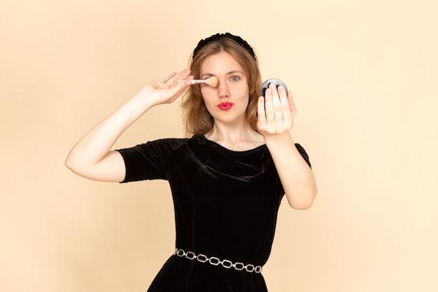 Una giovane femmina di vista frontale in vestito nero con la cinghia della catena che fa trucco sul trucco beige della mascara di modo del fondo