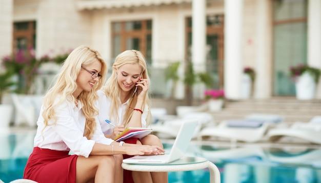 Una giovane imprenditrice che lavora da remoto su un laptop nel suo cortile di casa.