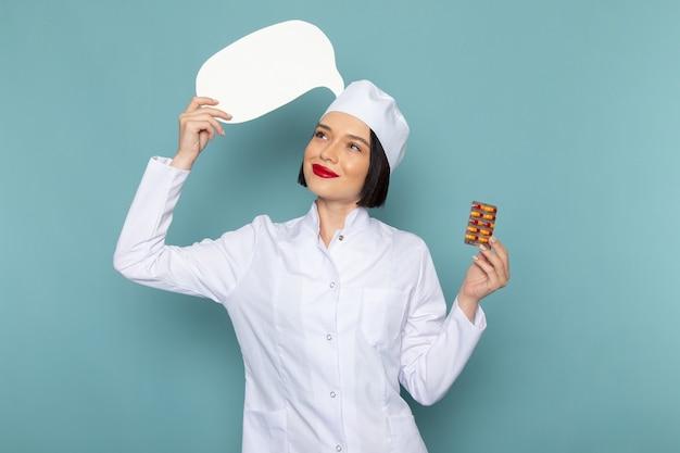 Una giovane infermiera femminile di vista frontale in pillole mediche bianche della tenuta del vestito e segno bianco sul medico dell'ospedale della medicina dello scrittorio blu