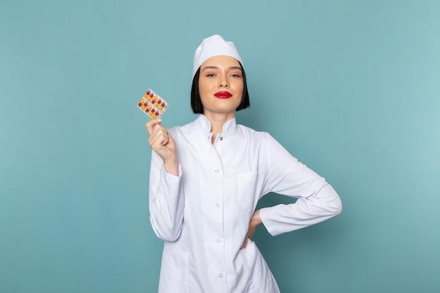 Una giovane infermiera femminile di vista frontale in pillole mediche bianche della tenuta del vestito sul medico dell'ospedale della medicina dello scrittorio blu