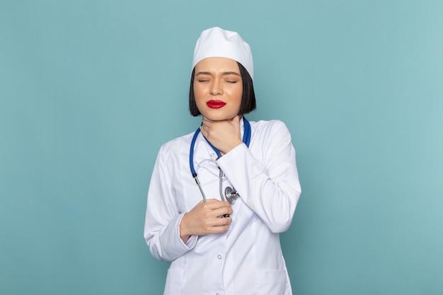 Una giovane infermiera femminile di vista frontale in tuta medica bianca e stetoscopio blu con problemi di gola
