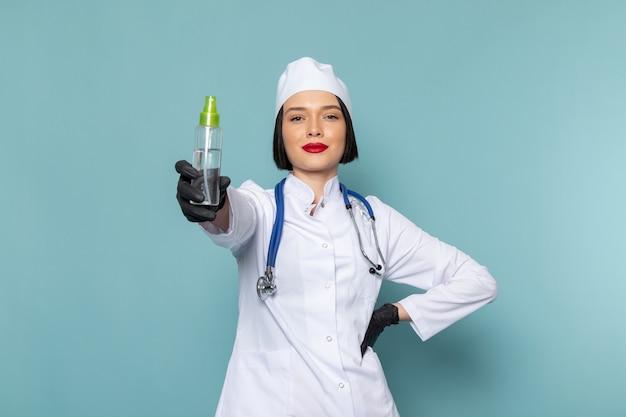 Una giovane infermiera femminile di vista frontale in vestito medico bianco e stetoscopio blu che tiene la boccetta dello spruzzo sul medico blu dell'ospedale della medicina dello scrittorio