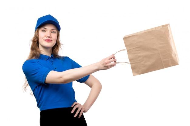 Una giovane lavoratrice femminile del corriere femminile di vista frontale del pacchetto di consegna dell'alimento della tenuta di servizio di consegna dell'alimento che sorride e che posa sul bianco