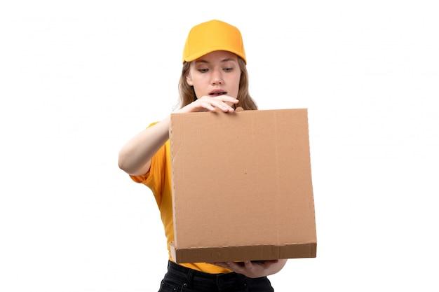 Una giovane lavoratrice femminile del corriere femminile di vista frontale del pacchetto sorridente dell'alimento della tenuta di servizio di distribuzione di alimenti su bianco
