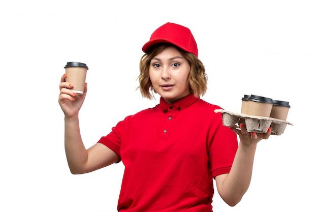Una giovane lavoratrice femminile del corriere femminile di vista frontale delle tazze di caffè della tenuta di servizio di distribuzione dell'alimento su bianco