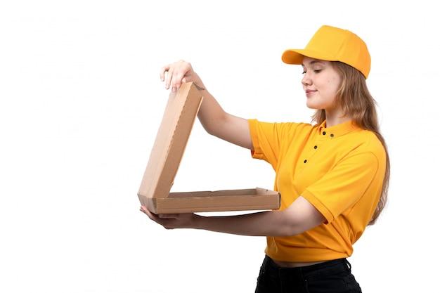 Una giovane lavoratrice femminile del corriere femminile di vista frontale di servizio di consegna dell'alimento che sorride tenendo un contenitore di pizza vuoto su bianco