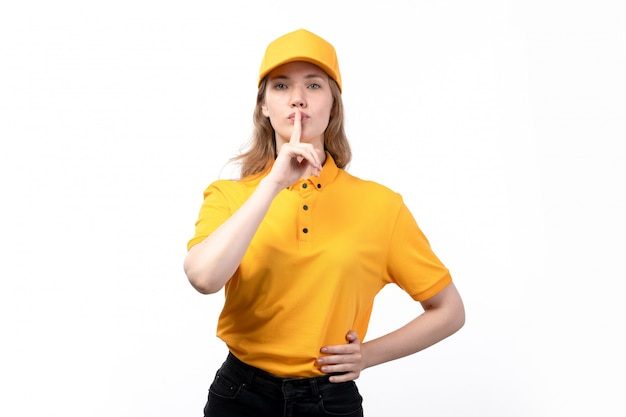 Una giovane lavoratrice femminile del corriere femminile di vista frontale di servizio di distribuzione di alimenti che mostra il segno di silenzio su bianco