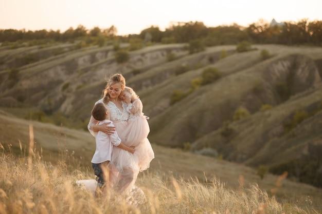 Una giovane madre con bambini cammina in un campo al tramonto