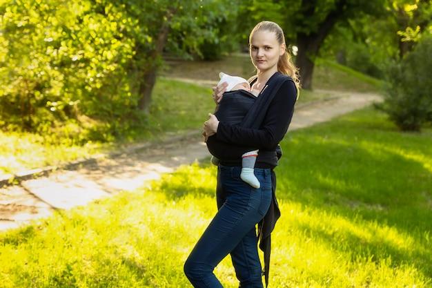 Una giovane madre con il suo bambino in una sciarpa a tracolla è in piedi in un parco.