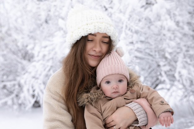 Una giovane madre con un bambino piccolo gioca nella neve