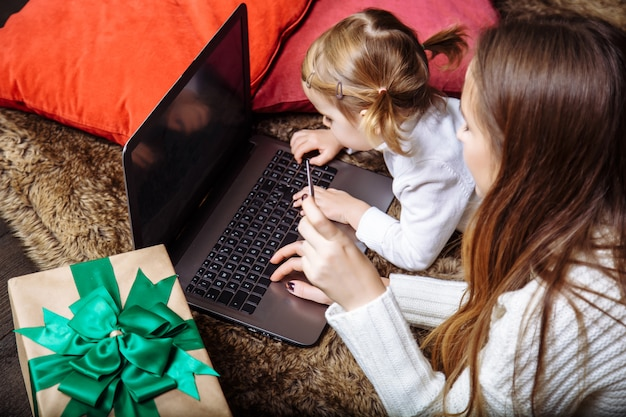 Una giovane madre con una figlia compra regali usando il laptop e la carta di credito