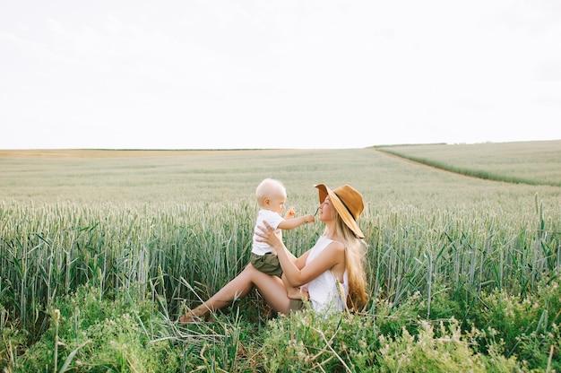 Una giovane madre e il suo piccolo bambino seduto vicino al grano su uno sfondo verde