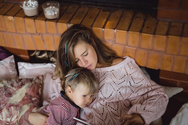 Una giovane madre e un figlio stanno leggendo un libro di fiabe vicino al camino.