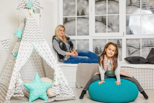 Una giovane madre in un maglione grigio e una figlia sono seduti nella stanza dei bambini in inverno.