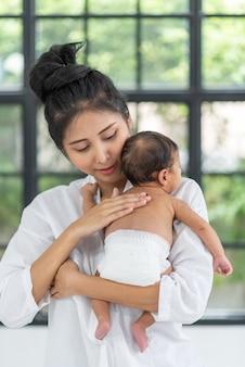 Una giovane madre porta un bambino