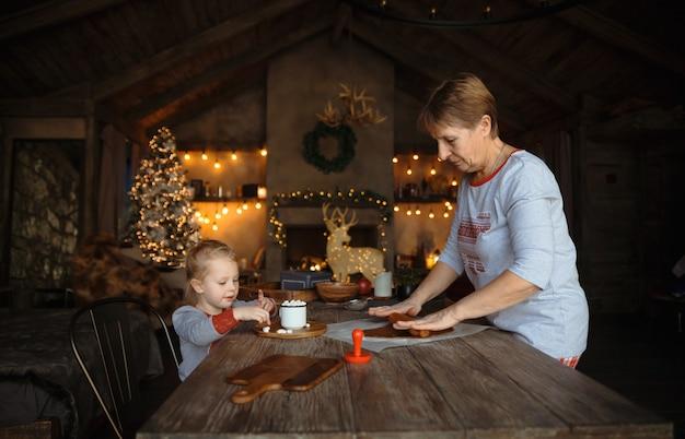 Una giovane nonna e sua nipote cucinano insieme i biscotti.