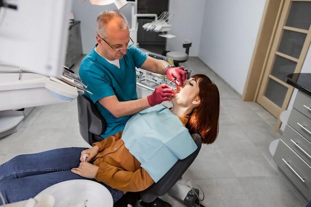 Una giovane paziente si prende cura di un dentista nell'ufficio del dentista. concetto di persone, medicina, stomatologia e assistenza sanitaria