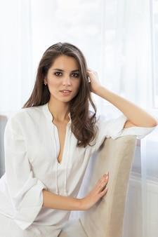 Una giovane ragazza attraente con i capelli lunghi è seduta in una vestaglia bianca sul letto.
