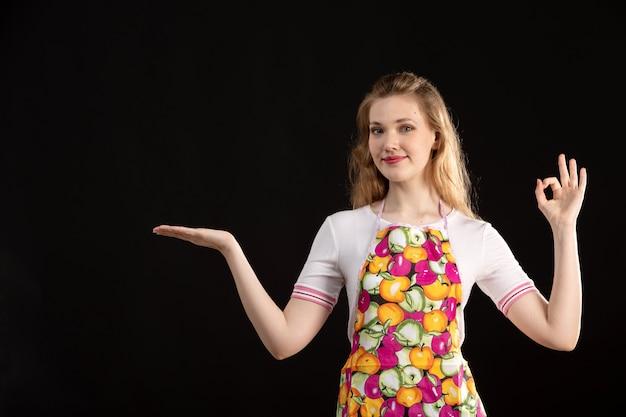 Una giovane ragazza attraente di vista frontale in capo variopinto che mostra i segni della mano che sorride sulla casalinga nera di pulizia del fondo