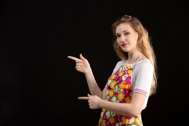 Una giovane ragazza attraente di vista frontale in capo variopinto che sorride sottolineando le dita sulla casalinga nera di pulizia del fondo