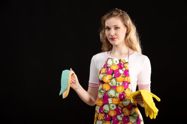 Una giovane ragazza attraente di vista frontale in guanti variopinti di pulizia d'uso sorridenti del capo sulla casalinga nera di pulizia del fondo