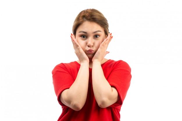 Una giovane ragazza attraente di vista frontale in maglietta rossa che indossa i fronti divertenti dei jeans neri sul bianco