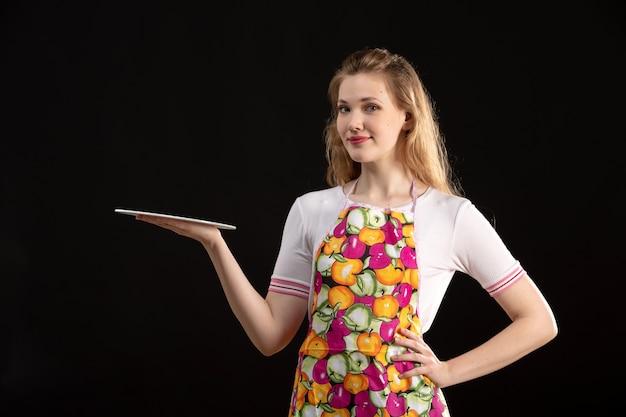 Una giovane ragazza attraente di vista frontale nella tenuta variopinta del capo dipinge sorridere sulla casalinga nera di pulizia del fondo
