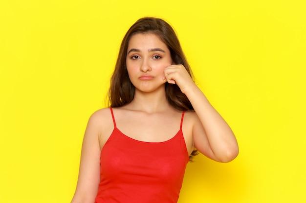 Una giovane ragazza bella vista frontale in camicia rossa e blue jeans, togliendosi la guancia