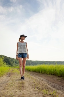 Una giovane ragazza bionda caucasica in pantaloncini, una maglietta e un cappello cammina lungo un sentiero in mezzo al campo e distoglie lo sguardo.