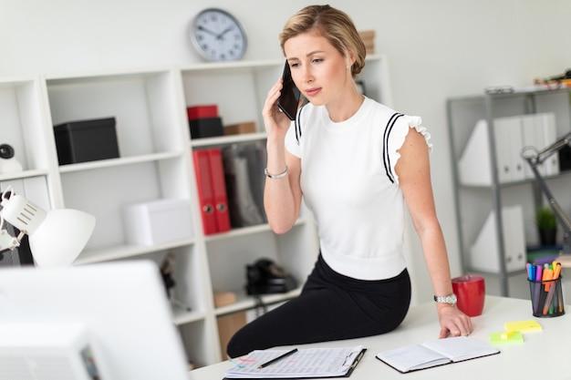 Una giovane ragazza bionda è seduta alla scrivania in ufficio e parla al telefono.