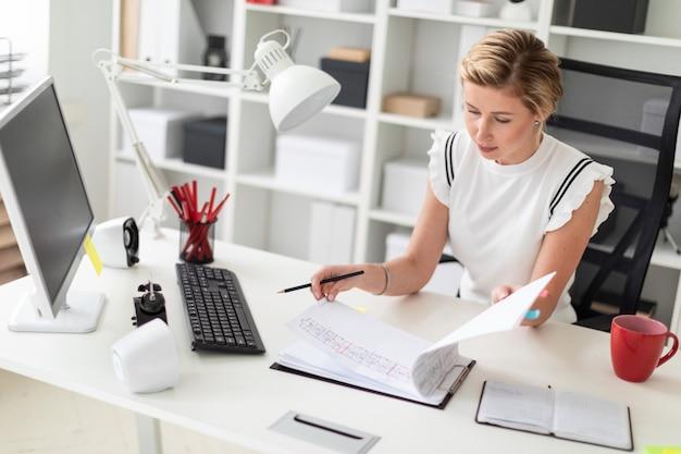 Una giovane ragazza bionda si siede a una scrivania del computer in ufficio