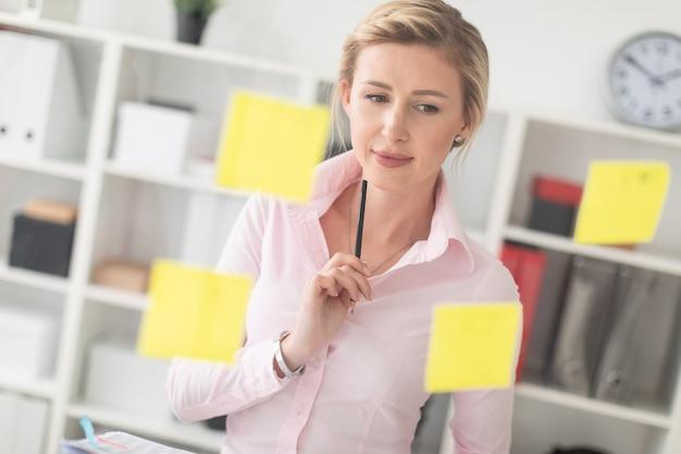 Una giovane ragazza bionda si trova in ufficio accanto a una lavagna trasparente con adesivi e detiene documenti