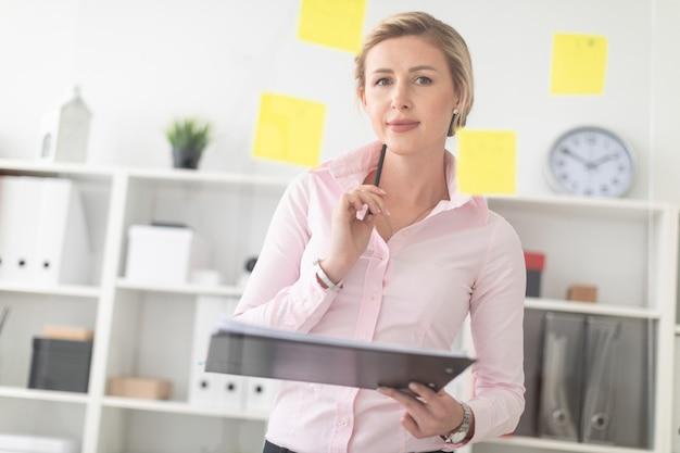 Una giovane ragazza bionda si trova nell'ufficio accanto a una lavagna trasparente con adesivi e tiene in mano documenti e una matita.