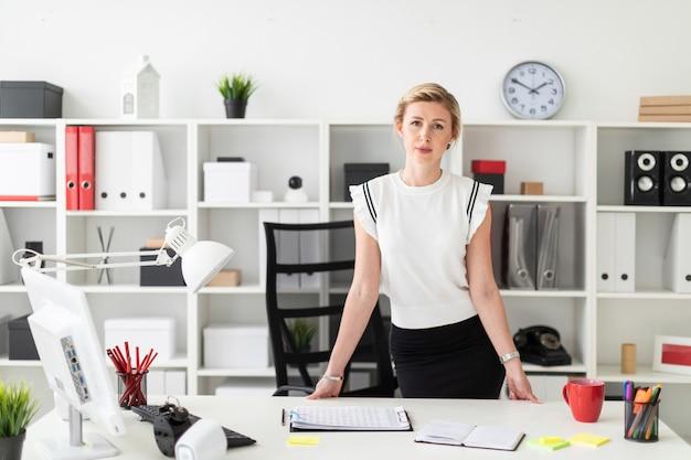 Una giovane ragazza bionda si trova vicino a un tavolo in ufficio.