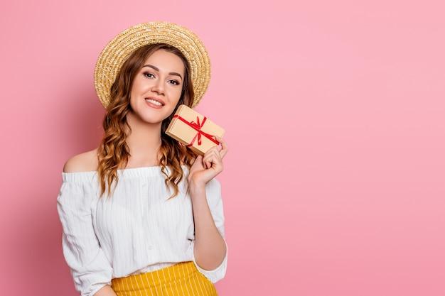 Una giovane ragazza caucasica in un abito bianco di cappello di paglia sorride e tiene una confezione regalo artigianale con un nastro rosso su una parete rosa. la ragazza felice abbraccia una scatola con un regalo
