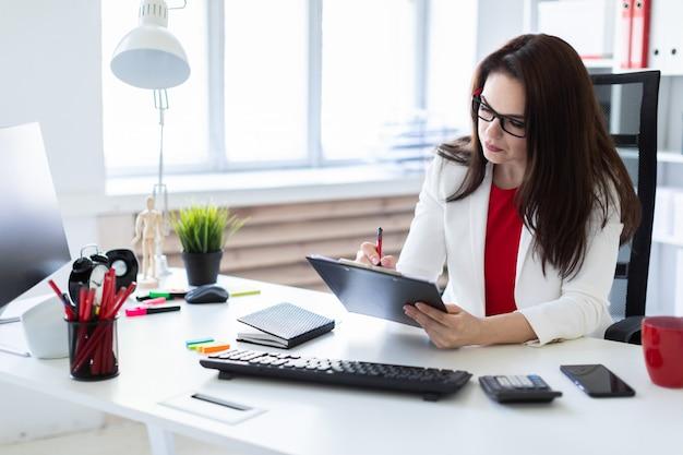 Una giovane ragazza che lavora in ufficio alla scrivania del computer. prima di mentire documenti.
