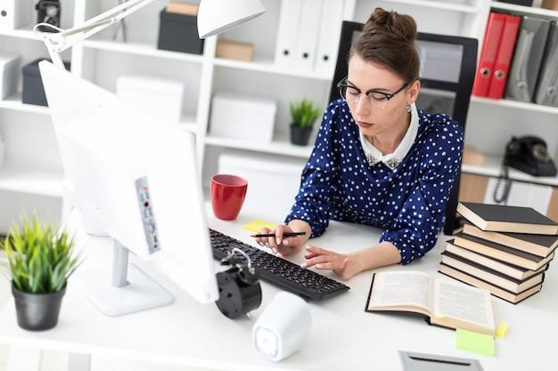 Una giovane ragazza con gli occhiali si siede in ufficio al tavolo e stampa sulla tastiera.